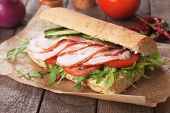 Submarine sandwich with smoked ham, tomato and rocket salad