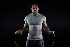 stock photo of roping  - Masculine man skipping rope in dark - JPG