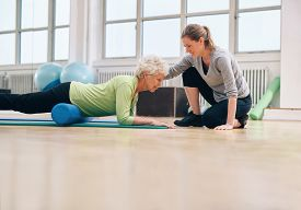 foto of therapist  - Senior woman exercising with a foam roller being assisted by personal instructor at gym - JPG