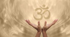 stock photo of om  - Female healing hands reaching up towards a soft focus Om symbol on a pale golden energy formation background - JPG