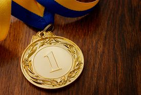pic of gold medal  - Gold medal in the foreground on yellow blue ribbon - JPG