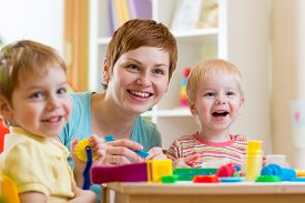 stock photo of child development  - woman teaches children handcraft at kindergarten or playschool or home - JPG