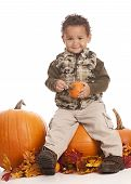 foto of gourds  - Adorable toddler sitting on top of a giant pumpkin and holding a gourd - JPG