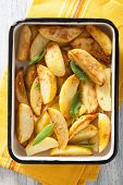 stock photo of baked potato  - baked potato wedges in enamel baking dish - JPG