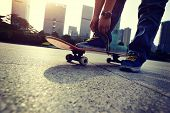 stock photo of skate board  - young skateboarder tying shoelace at skate park - JPG