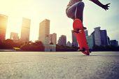 stock photo of skateboarding  - skateboarder doing skateboarding trick ollie on city - JPG