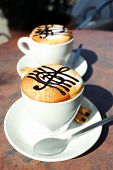 pic of clefs  - Cups of cappuccino with treble clef on foam on table in cafe - JPG