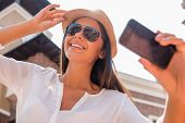 stock photo of funky  - Low angle view of beautiful young funky woman adjusting her hat and making selfie while standing outdoors - JPG