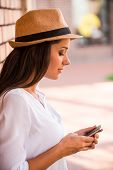 foto of funky  - Side view of thoughtful young woman in funky hat typing something on mobile phone while leaning at the wall outdoors  - JPG