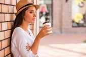 image of funky  - Side view of thoughtful young woman in funky hat holding cup with hot drink and looking away while leaning at the wall outdoors - JPG