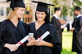 stock photo of graduation gown  - Two happy women in graduation gowns looking at the mobile phone together and smiling while two men standing in the background - JPG