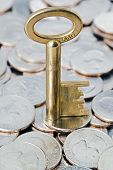 stock photo of golden coin  - Golden key on coins NOTE FOR INSPECTION: 66G is the weight of the key Business and finances conceptual image ** Note: Shallow depth of field - JPG