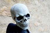 foto of eye-sockets  - Scale model of a human skull in front of the old wall - JPG