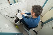 image of wheelchair  - High Angle View Of Man On Wheelchair Washing Hands In Bathroom - JPG