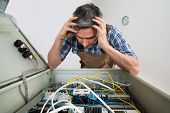pic of fuse-box  - Portrait Of A Confused Electrician Looking At Fuse Box - JPG