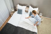image of housekeeper  - Young Female Housekeeper Changing Bedding In Hotel Room - JPG