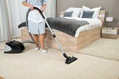 image of housekeeper  - Female Housekeeper Cleaning With Vacuum Cleaner In Hotel Room - JPG