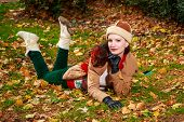 stock photo of fallen  - Attractivve young woman in fashionable outfit roll across fallen leaves - JPG