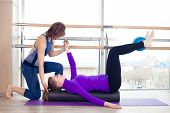 stock photo of personal care  - Aerobics Pilates personal trainer helping women group in a gym class - JPG