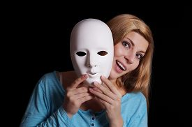 stock photo of pantomime  - young woman removing plain white mask from her face - JPG