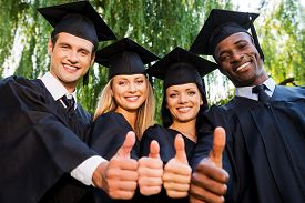picture of graduation gown  - Low angle view of four college graduates in graduation gowns standing close to each other and showing their thumbs up - JPG