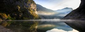 stock photo of reflections  - Extraordinary fairy tale mythological mountain lake scenery in a glacial valley with sun shining to the rocky and morning mist above the lake surface with perfect reflection - JPG