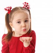 stock photo of valentines day  - Portrait of a cute preschool girl blowing a kiss wearing red and pigtails dressed for Valentines day - JPG