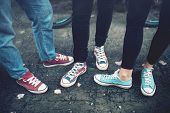 Постер, плакат: Young Rebel Teenagers Wearing Casual Sneakers Walking On Dirty Concrete Canvas Shoes And Sneakers
