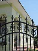 beautiful wrought-iron black metal fence on a bright sunny day against a beautiful building