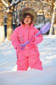 Girl in snowsuit standing in deep snow