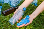 Постер, плакат: Hand Of Woman With Plastic Bottle And Bottle Caps Littering Of Environment