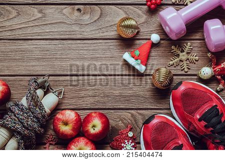poster of Fitness healthy and active lifestyles love concept dumbbells sport shoes skipping rope or jump rope and apples with Christmas decoration items on wood background. Exercise Fitness and Working Out Merry Christmas and Happy new year concept.