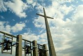 stock photo of pio  - bell tower with a crucifix on the summer sky with clouds - JPG