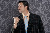 salesperson portrait pointing with thumb finger on wallpaper background