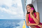 Cruise ship woman using mobile cellphone calling on travel vacation. Asian girl on travel holidays.  poster