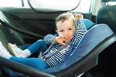 Baby Smile In A Safety Car Seat. Security. One Year Old Child Girl In Blue Wear Sit On Auto Cradle. poster