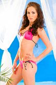 Glamour style photo of beautiful young girl in pink bikini posing in summerhouse on beach.