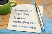 Successful investing is about managing risk, not avoiding it - handwriting on a napkin with a cup of poster