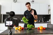 Smiling young man filming his video blog episode about healthy food cooking while standing and showi poster