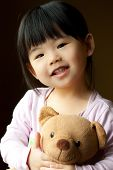 stock photo of teddy-bear  - Smiling little child holding a teddy bear in her hand - JPG