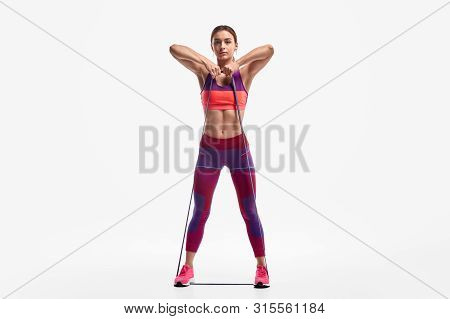 poster of Full Length Determined Young Woman In Sportswear Looking At Camera And Pulling Resistance Band To Ch