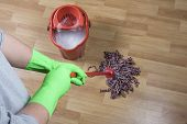 picture of dust mite  - a cleaner is mopping wooden parquet floor - JPG