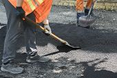 Worker Man Lays Asphalt Road Repair Road Paving Yellow Sun Ray Light. A Man In Overalls Is Laying As poster
