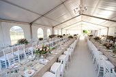picture of wedding feast  - The inside of a massive white wedding tent with tables and chairs already in position - JPG
