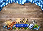 Rustic background for Oktoberfest with letters Ozapft is! - translation: The beer is tapped, whit poster