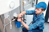 Young man in workwear using pliers while installing water filtration system poster