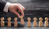 The Hand Of A Businessman Takes A Wooden Figure Of A Man. Business Tactics And Strategy, Management, poster