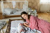 Happy Mother With Baby At Home. Young Mother Holding Her Newborn Baby. A Woman And A Newborn Boy Are poster