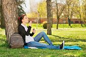 Blowing Soap Bubbles In The Park. Beautiful Young Student Girl Leaning On A Tree In A Meadow Blowing poster
