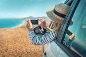 Happiness young woman sitting in white car and shoot with her phone camera beautifull ocean coastlin poster